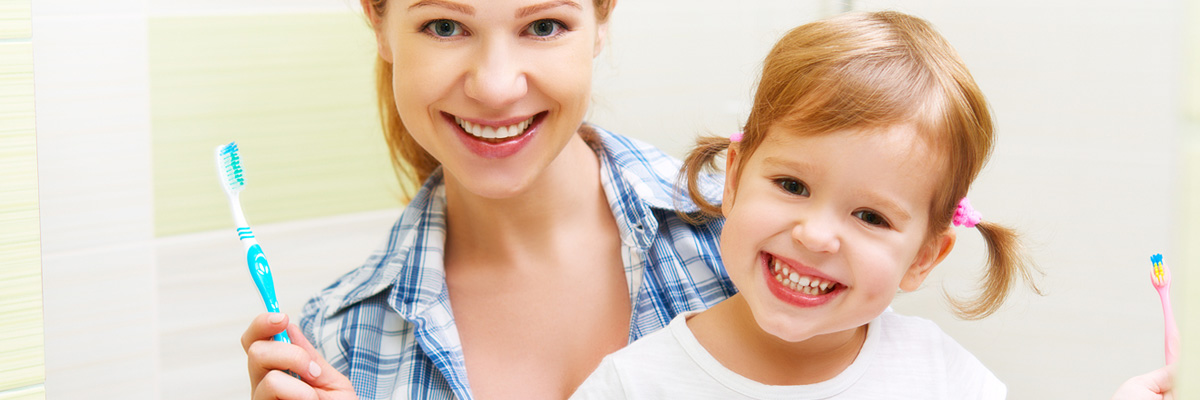Happy family mother and daughter child girl brushing her teeth