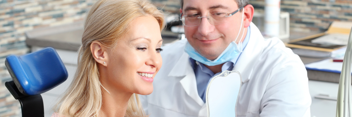beautiful blonde woman sitting at dentist and checking tooth whitening while male doctor holding in his hand a mirror.