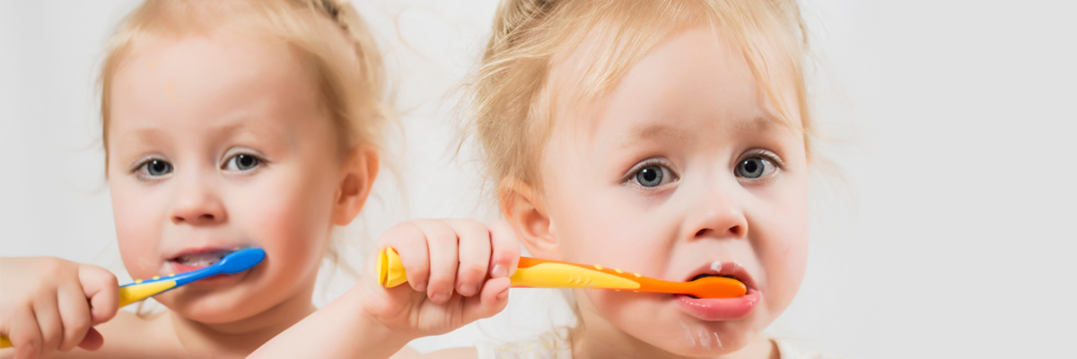 children brush their teeth, white background. two funny twins